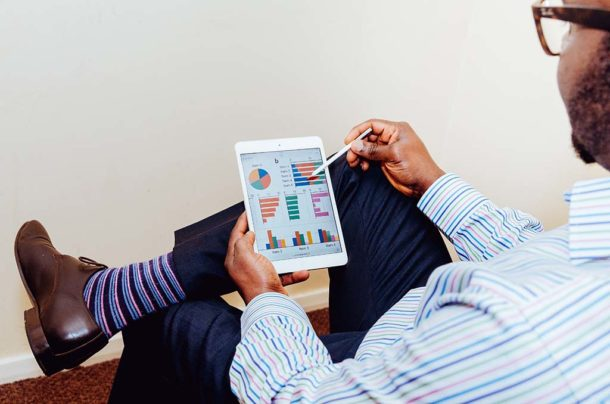 mężczyzna śledzący wyniki handlu internetowego na tablecie